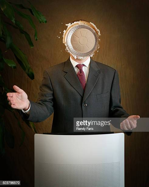 businessman receiving a pie in the face - pie in the face stock pictures, royalty-free photos & images