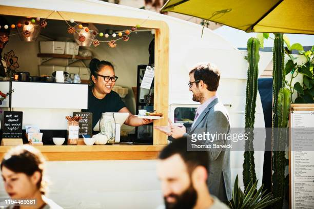 businessman receiving food order from owner of food truck - food truck fotografías e imágenes de stock