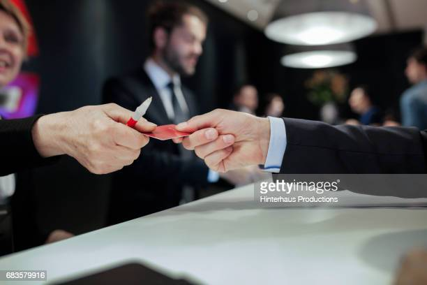 businessman receiving hotel room keycard - passing giving stock photos and pictures
