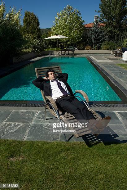 Homme d'affaires allongé sur une chaise longue près de la piscine, Zekeriyaköy, Istanbul, Turquie