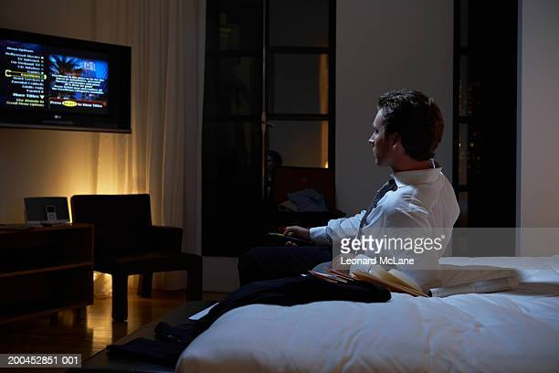 Businessman reclining on bed watching television, night