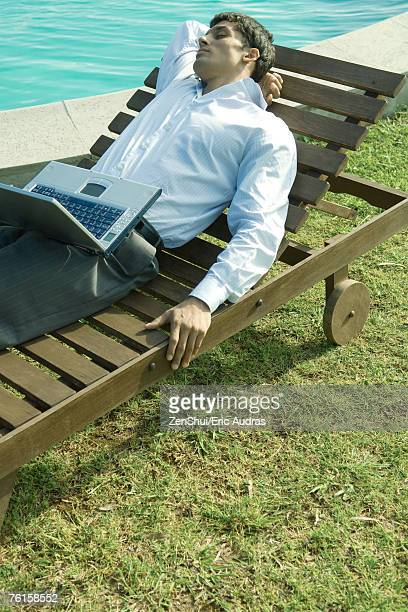 Businessman reclining on lounge chair, laptop on lap, eyes closed