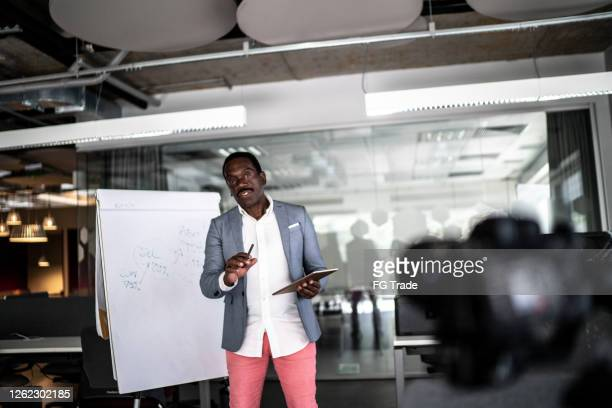 businessman recording a video in the office - founder stock pictures, royalty-free photos & images