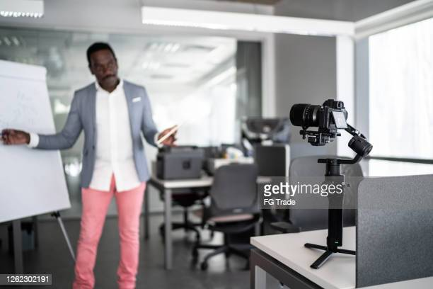 businessman recording a video in the office - press room stock pictures, royalty-free photos & images