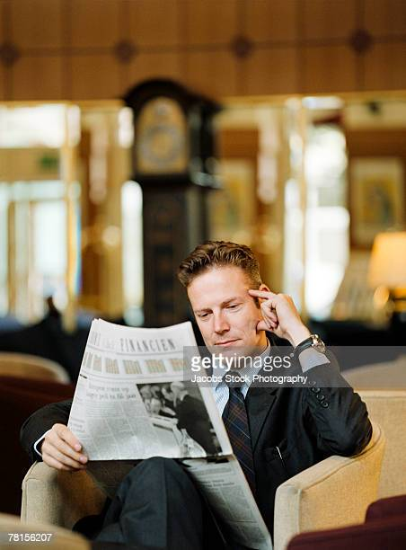Businessman relaxing and reading a newspaper