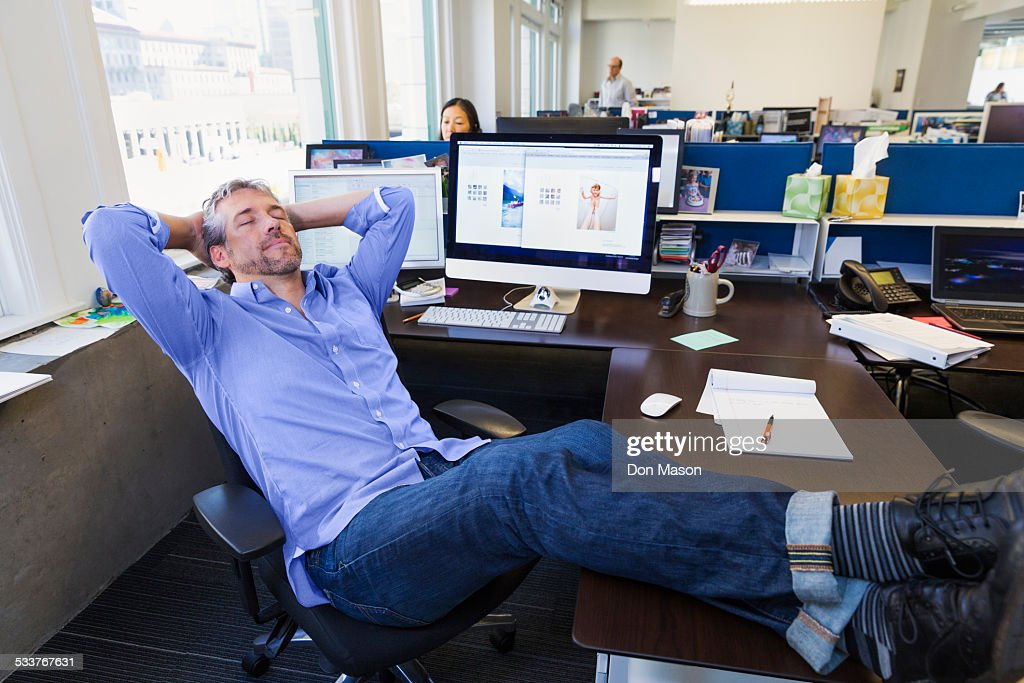 Businessman relaxing at desk in office : Foto stock