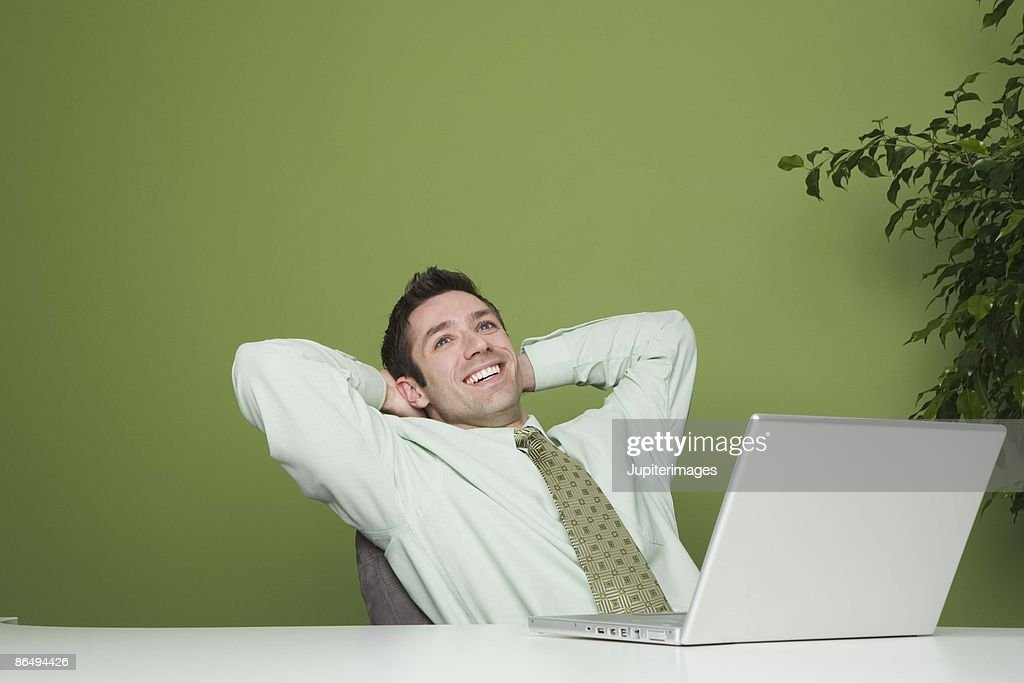Businessman relaxing by laptop : Stock Photo