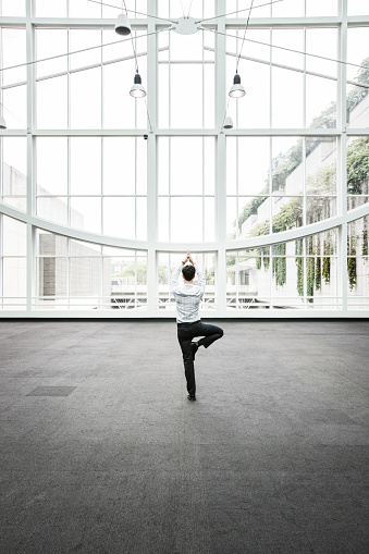 Businessman relaxing doing a yoga pose in a large open glass covered walkway. - gettyimageskorea
