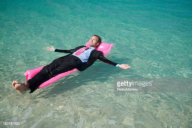 Businessman Relaxing Floating on Pink Pool Raft