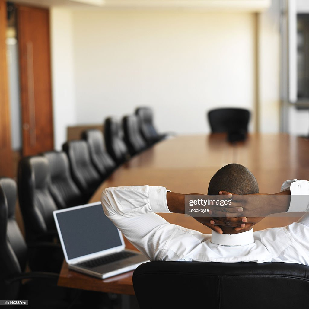businessman relaxing in an empty conference room with a laptop in front of him : Photo