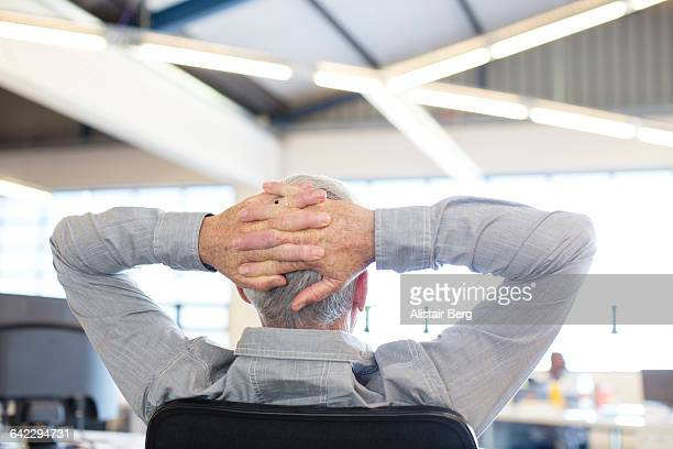 Businessman relaxing in an open plan office