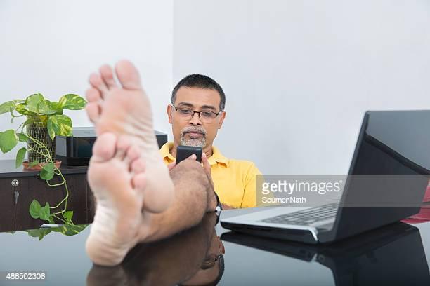Empresario relajante en su oficina usando Vestimenta informal