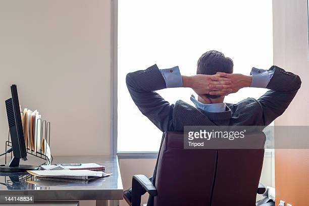 Businessman relaxing in office chair, rear view