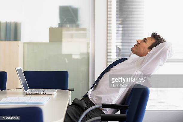 businessman relaxing in office - hugh sitton stock-fotos und bilder
