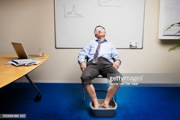 Businessman relaxing in office, wearing facemask, soaking feet