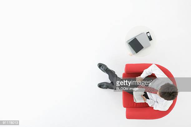 Businessman relaxing on couch, view from above, studio shot