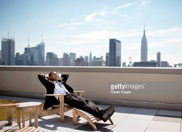 businessman relaxing on lounge chair against sky - sun lounger stock pictures, royalty-free photos & images