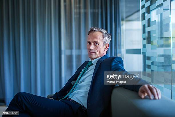 Businessman relaxing on sofa in office lobby
