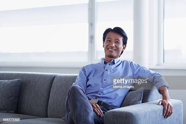 Businessman relaxing on sofa in office