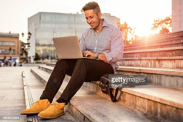 Businessman relaxing on stairs in the city and using laptop.