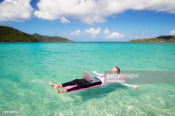 Businessman Relaxing Spreadeagle on Tropical Bay with Laptop