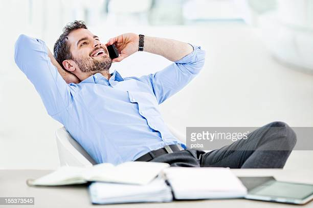 Businessman relaxing while  talking on a mobile phone in armchair