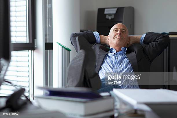 Businessman relaxing with feet on desk