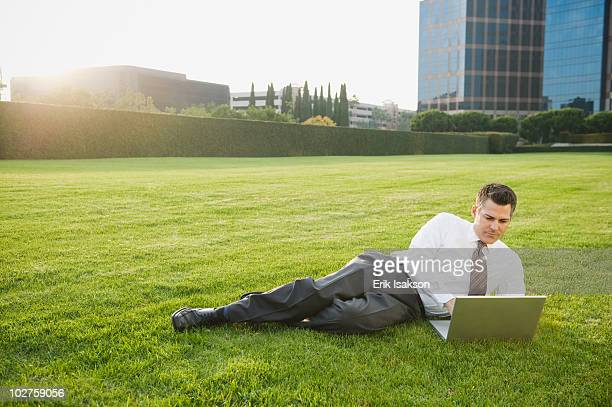 Businessman relaxing with laptop on lawn