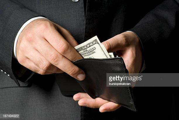 businessman removing american bill from black leather wallet - exceed and excel stock pictures, royalty-free photos & images