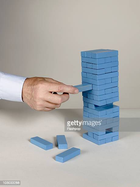 Businessman removing building block