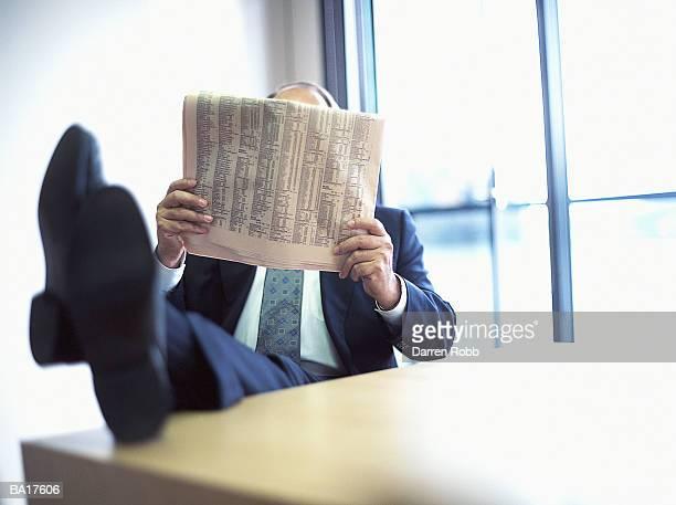 businessman resting feet on desk, newspaper obscuring face - viso nascosto foto e immagini stock
