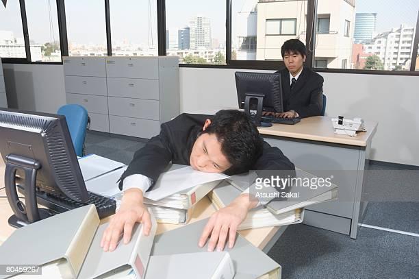 Businessman resting head on office desk