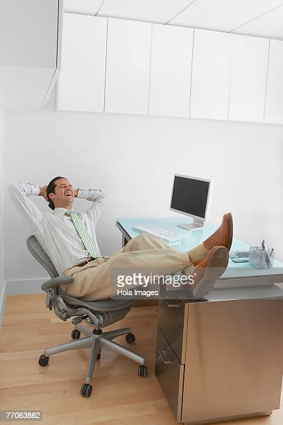 Businessman resting his legs on the desk and laughing in an office