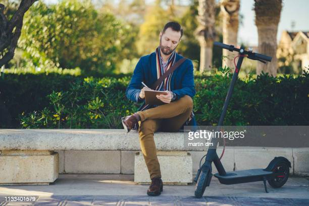businessman resting in the city park after scooter riding - electric scooter stock pictures, royalty-free photos & images