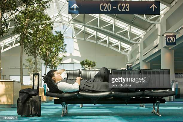 Businessman resting on chairs in airport.