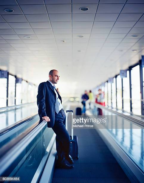 Businessman Resting on Moving Sidewalk