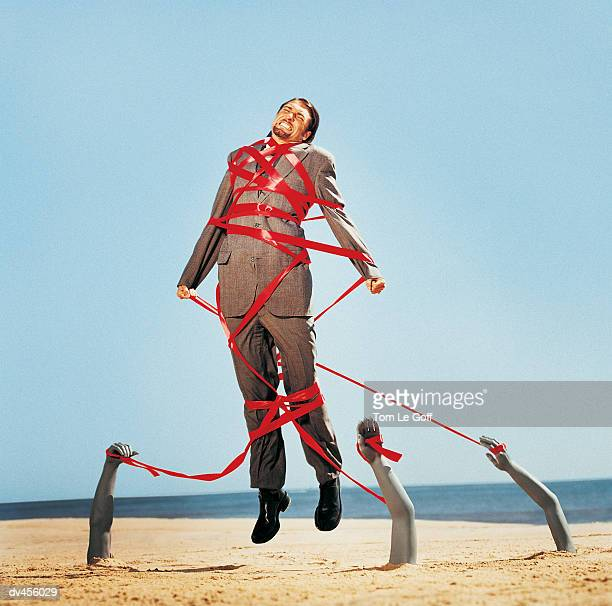 businessman restrained by red tape - restraining stock pictures, royalty-free photos & images
