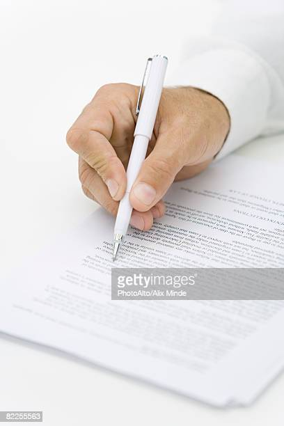businessman reviewing contract with pen, cropped view of hand - verification stock pictures, royalty-free photos & images