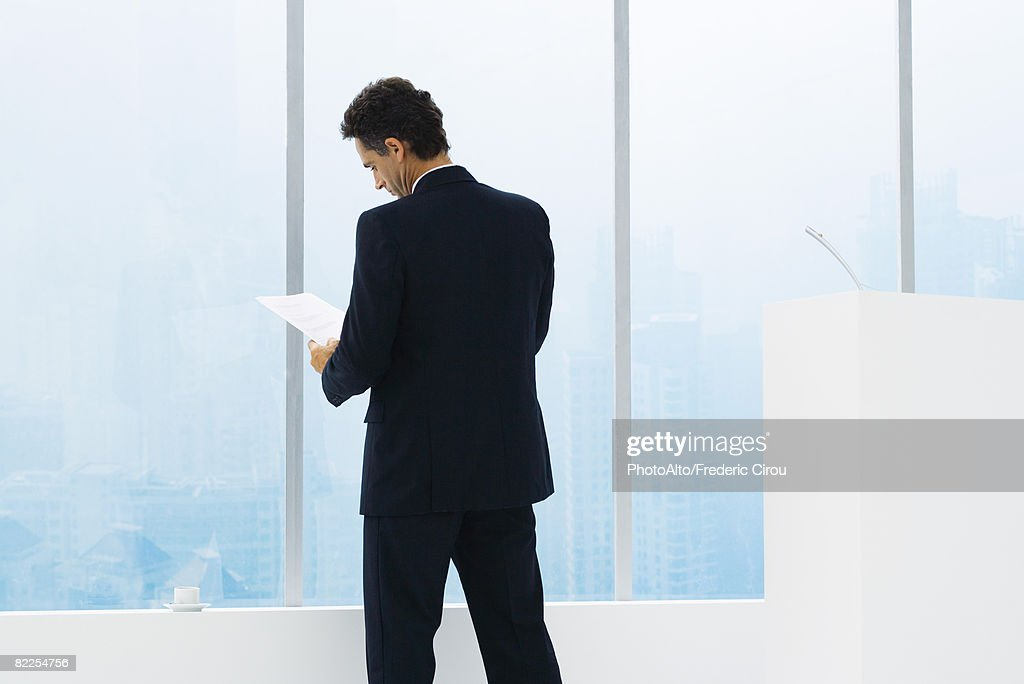 Businessman reviewing document, standing, rear view : Stock Photo