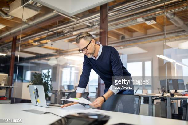 businessman reviewing few reports in office - papierkram stock-fotos und bilder