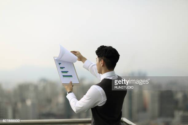 Businessman reviewing notes on clipboard