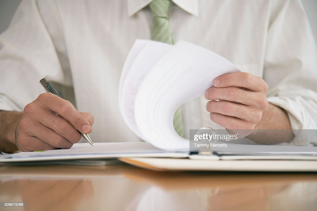 Businessman reviewing paperwork : Stock Photo