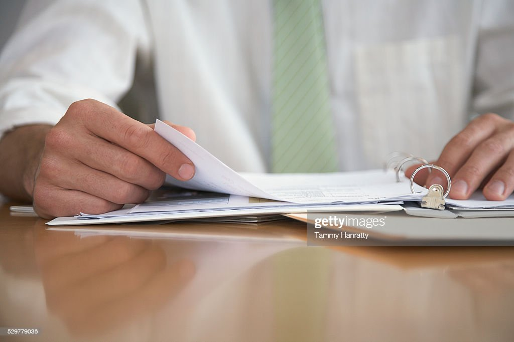 Businessman reviewing paperwork : Stock Photo