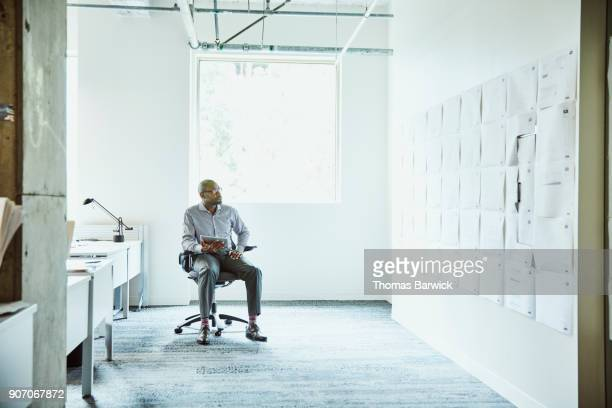 businessman reviewing project plans on office wall while working on digital tablet - finance and economy stock pictures, royalty-free photos & images