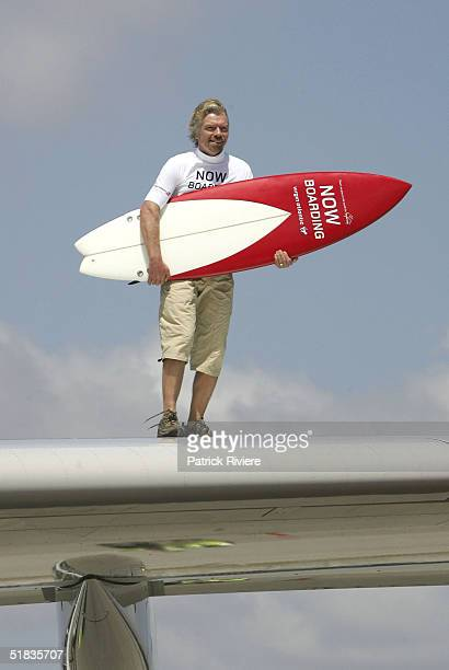 Businessman Richard Branson holds a surfboard as he stands on the wing of a Virgin Atlantic aircraft on his arrival to launch his new Virgin Atlantic...