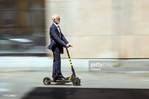 businessman riding a electric scooter in the city - electric scooter stock pictures, royalty-free photos & images