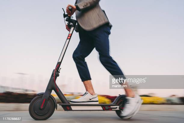 businessman riding a motor scooter in sofia - electric scooter stock pictures, royalty-free photos & images