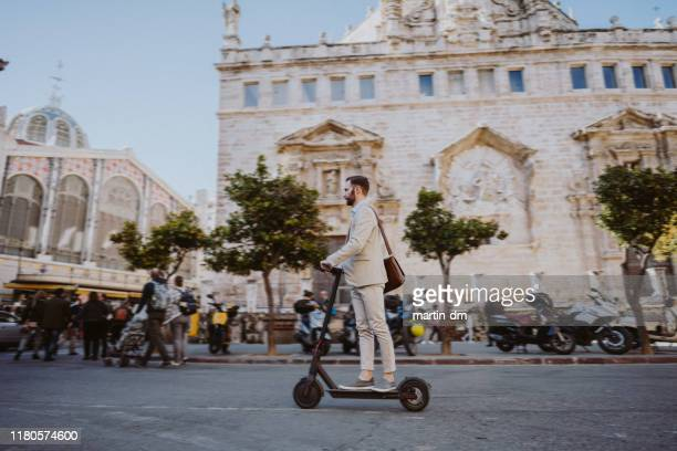 businessman riding a motor scooter in valencia - valencia spain stock pictures, royalty-free photos & images