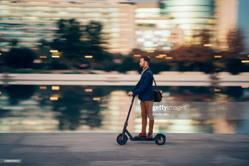 Businessman riding a scooter in the city : Stock Photo