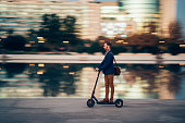 Businessman riding a scooter in the city